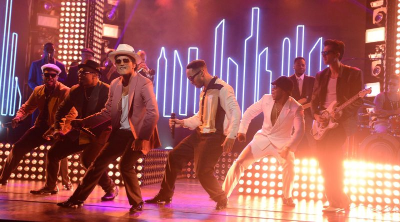 """Bruno Mars, in white fedora and pink jacket, and Mark Ronson, on guitar, perform """"Uptown Funk!"""" on Saturday Night Live."""